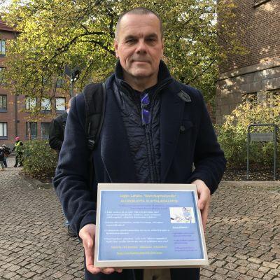 Mieshenkilö pitää kädessään taulua, jossa lukee kuntalaisaloite