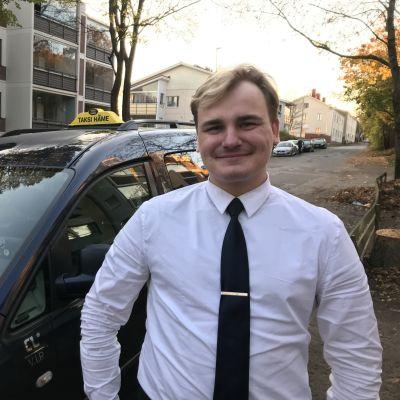 Hymyilevä taksinkuljetta seisoo autonsa edessä