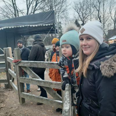 Pieni poika katselee eläinaitaukseen äitinsä sylistä Tampereen Tallipihalla nen ja Hanna-Riikka Saarinen