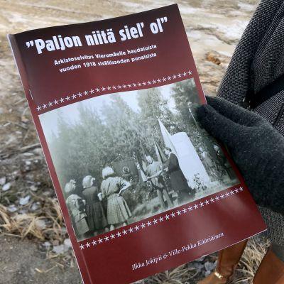 Suomen sisällissodasta Vierumäen taisteluista kertova kirja miehen kädessä