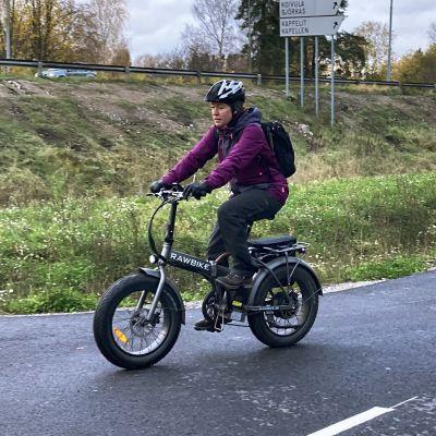 Pia cyklar på cykelväg med sin elcykel.