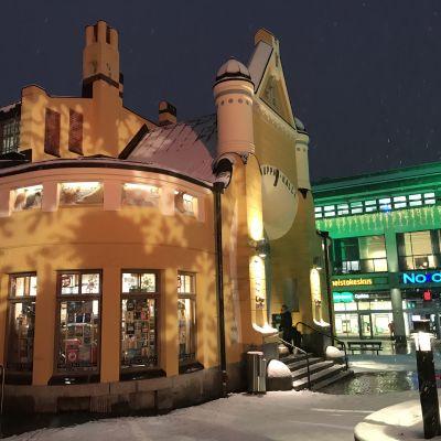 Kuopion kauppahalli ja takana oleva kiinteistö on valaistu joulun kunniaksi värivaloin.
