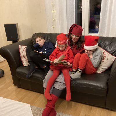 Äiti lukee lapsille jouluaiheista kirjaa.
