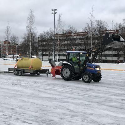 Traktori vetää vesisäiliötä Kuopionlahden kaukalossa Kuopiossa.