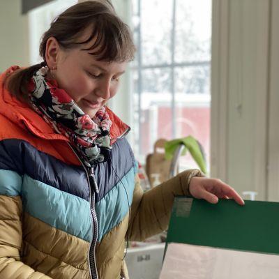 Noora Räsänen selaa infokasniota ikkunan ääressä.