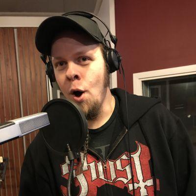 Lippalakkipäinen mies laulaa mikrofoniin
