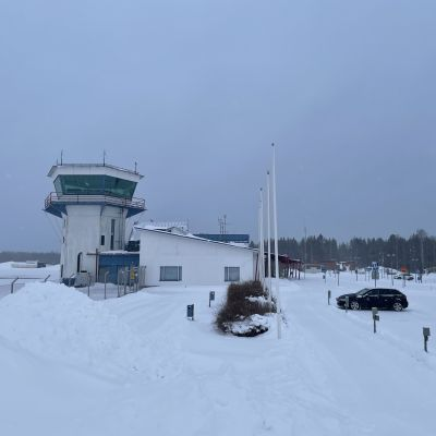 Hiljentynyt Kajaanin lentoasema ulkoapäin. Parkkipaikalla on vain pari autoa.