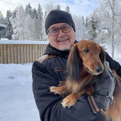 Mies koira sylissään talvisessa lumimaisemassa