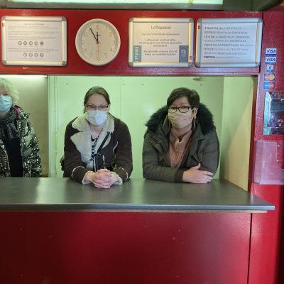 kolme naista elokuvateatterin lippuluukun takana