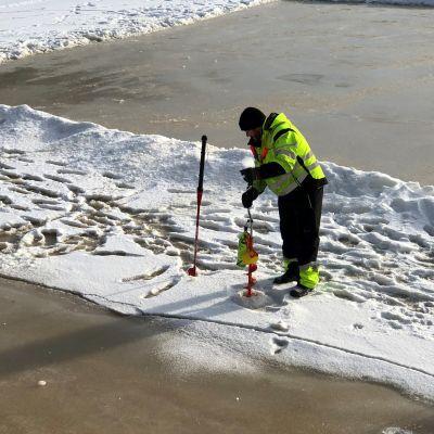 Antti Aalto mittaa Aurajoen jäätä.
