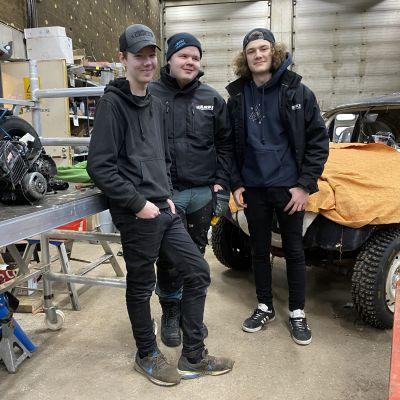 Kolme loppilaista ysiluokkalaista seisoskelee konehallissa.