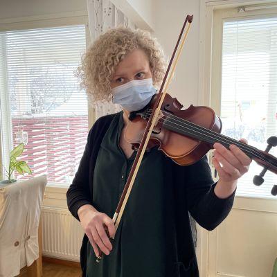 Nainen soittaa viulua olohuoneessa.
