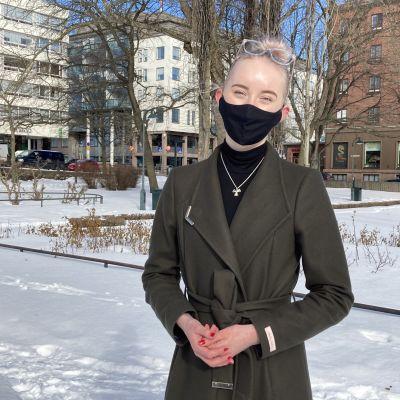 Nuori nainen seisoo lumisessa puistossa maski kasvoillaan