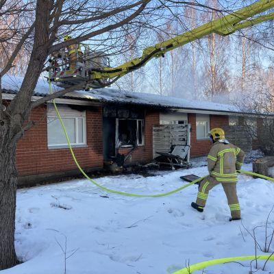 Pelastuslaitos sammuttaa rivitalossa tulipaloa