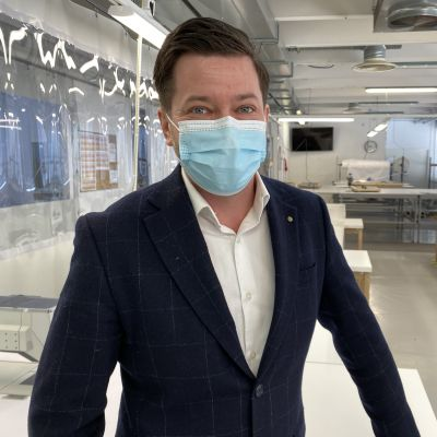 Siniseen puvuntakkiin pukeutunut lyhythiuksinen mies katsoo kameraan kirurgine suu- nenäsuoja kasvoillaan. llaan