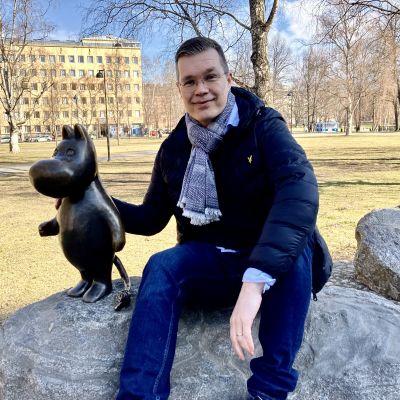 Mies istuu puistossa kivellä Muumipeikko-patsaan vieressä.