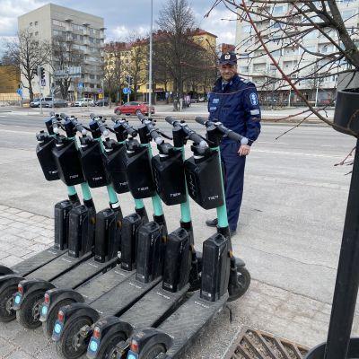Ylikomissario Jouni Takala Hömeen poliisista tutkii sähköpotkulautoja Lahdne Matkakeskuksessa.