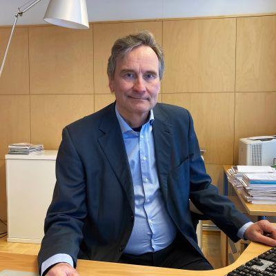Kittilän kunnanjohtaja Antti Jämsén istuu työpöytänsä takana ja hymyilee.