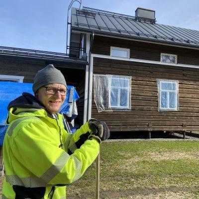 Nuori mies seisoo rakenteilla olevan uuden hirsitalon edessä