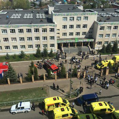 En trevåningsbyggnad omgiven av ambulanser och polisfordon.