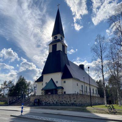 Rovaniemen kirkko kesäpäivänä, aurinko paistaa kirkontornin takaa