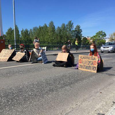 mielenosoittajat istuvat kylttien kanssa sillalla