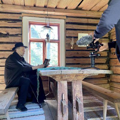 Lasse Lyytikäinen lukee kirjaa pöydän ääressä sekä  kameran edessä.
