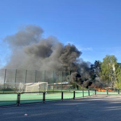 Musta savupilvi nousee tulipalosta Rovaniemen keskuskentän ylle