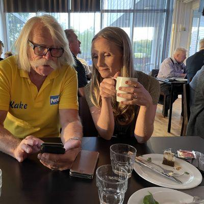 Kauko Isomäki ja Kaisa Garedew katsovat puhelimesta vaalituloksia perussuomalaisten kuntavaalivalvojaisissa 2021.