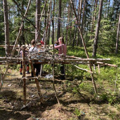 Nuorista puunrungoista rakennettu iso majarakennelma metsässä. Taustalla aikuisia ja lapsia rakentamassa.