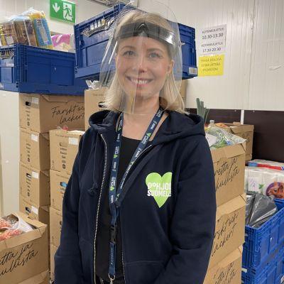 Oulun Linnanmaan ja Limingantullin Prismojen johtaja Anna Kela verkkokauppatilausten perusteella pakattujen tuotelaatikoiden edessä.
