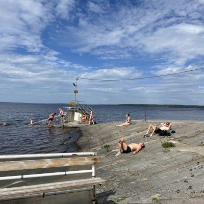 Tampereen Rauhaniemen rannan kalliot etualalla, taustalla uimarappuset