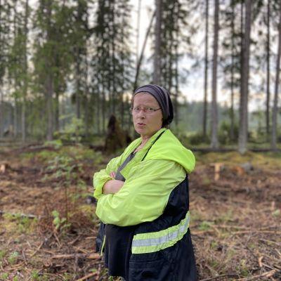 Tiina Pesonen myrskyn riepotteleman metsän laidassa.