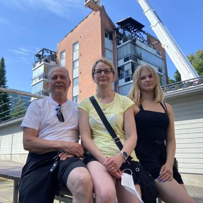 Harri, Johanna ja Viivi Qvintus katsovat kameraan palaneen kotitalonsa edustalla.