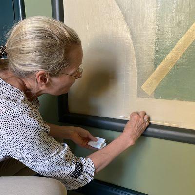 Taidekonservaattori Nina Robins tutkii seinämaalauksen kuntoa