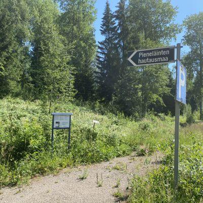 Kuvassa on metsää ja peltoa sekä kyltti, jossa lukee pieneläinten hautausmaa