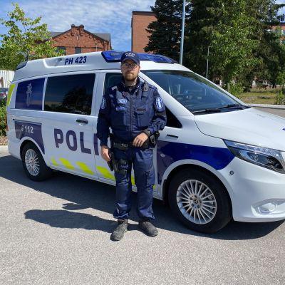 Ylikonstaapeli Joonas Salo Hämeen poliisista seisoo uuden sähköllä kulkevan poliisiauton edessä.
