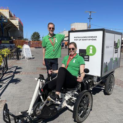 Matkailuneuvoja Jenni Honkanen istuu Oulun matkailun konttipyörässä ja matkailuneuvoja Jussi Pakonen seisoo pyörän vierellä Oulun torilla.