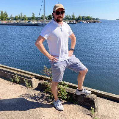 mies seisoo laiturilla aurinkolasit päässä