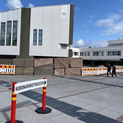 Rovaniemen kaupungintalo ja kyltti, joka opastaa koronarokotukseen