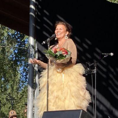Arja Koriseva hymyilee palkinto ja kukkapuska kädessään