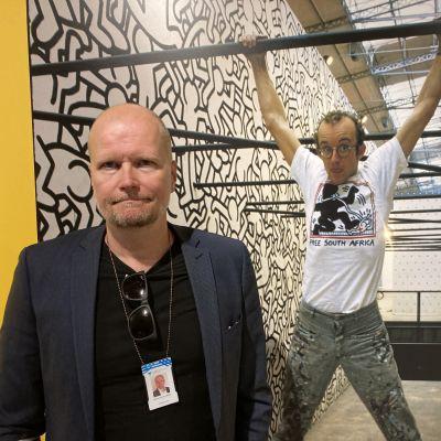 Mies seisoo valokuvan edessä näyttelyssä
