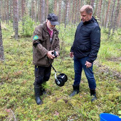 Mies esittelee toiselle akkukäyttöistä, varrellista marjanpoimuria