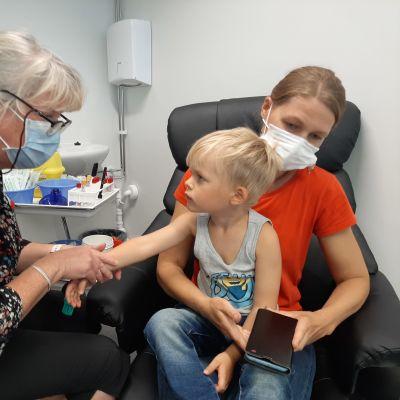Pojke tittar på en vårdare som precis ska ge honom vaccin.