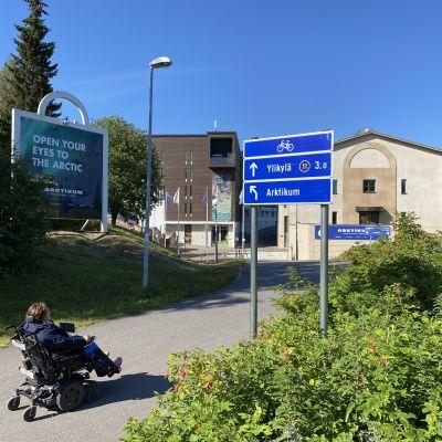 Pyöräteiden uusi opaste, edustalla henkilö pyörätuolissa, taustalla Artkikum.