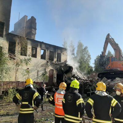 Brandmän och rykande ruin.