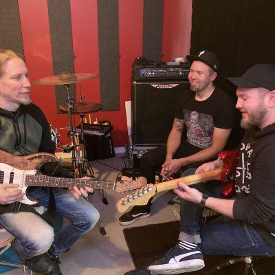 Sami Jänikselä, Jukka Rutanen ja Ilkka Huhtala soittelemassa treenikämpässä.