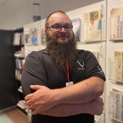 Muistiasiantuntija Marko Mustiala sseisoo kädet puuskassa sanomalehtihyllyn edessä Yle Hämeenlinnan toimituksessa Muistiviikolla 22.9.2021.