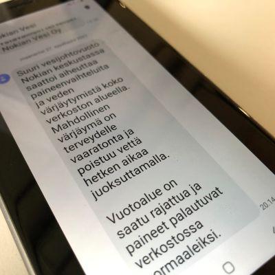 Kuva puhelimesta, johon on tullut palveluviesti vesikatkosta