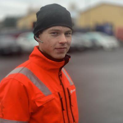 En ung man med mössa och headset är klädd i orangea arbetskläder